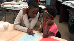 a third grade student and her family member work on creating their story together.