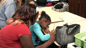 A third grade student sits and writes hers story as a family member looks over her shoulder.