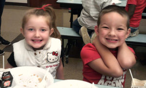 Two Jefferson students smile for the camera after they have finished eating their pancakes.