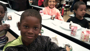 a Jefferson student smiles for the camera after he has finished his pancake breakfast.