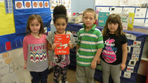 Students show the book Green Eggs and Ham.