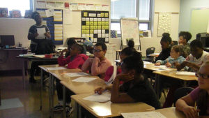 Students sit at their desks while the teacher explains their next activity.