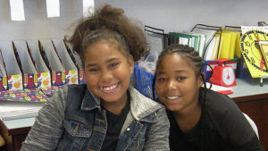 Two students smile for the camera while working at their desks.