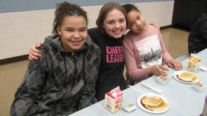 Students pause for a photo while enjoying their pancakes.