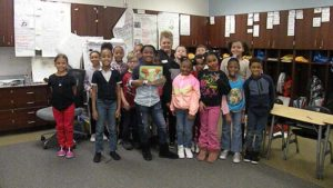 A class takes a picture with their guest reader.